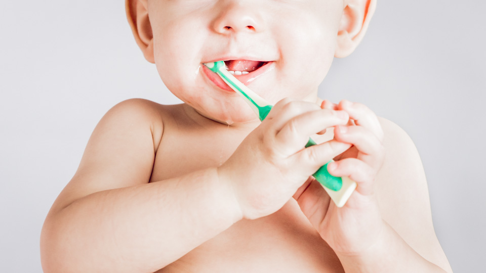 A four-month-old baby brushing his teeth without toothpaste.