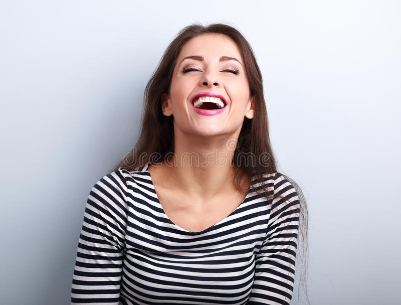 Happy natural laughing young casual woman with wide open mouth a royalty free stock images