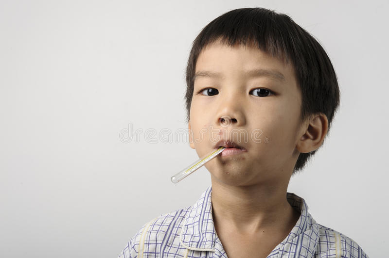 Kid has a herpes on mouth and measuring the fever stock image