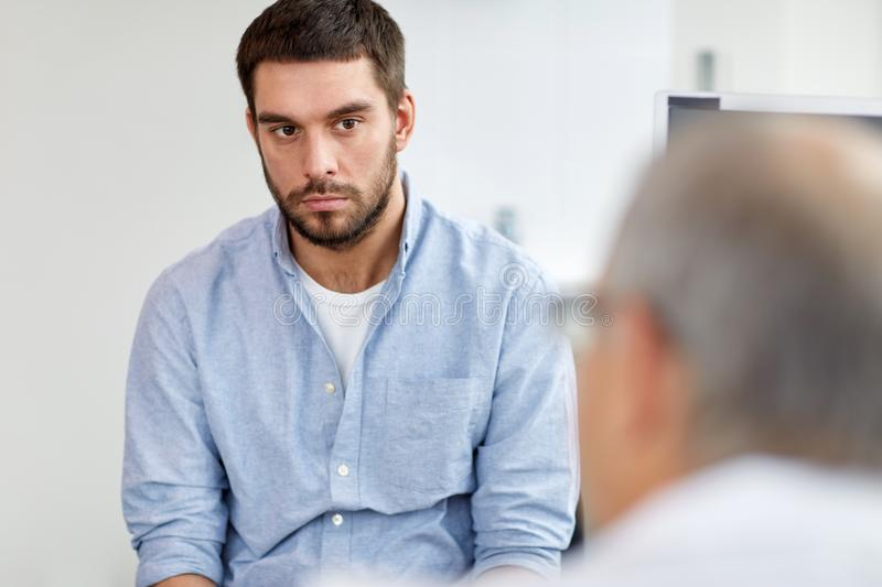Young male patient talking to doctor at hospital royalty free stock image