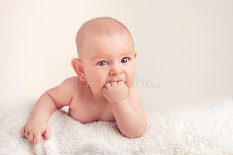 Small cute funny baby infant teething with face expression hands and fingers in mouth sore gums. Soothe royalty free stock photography