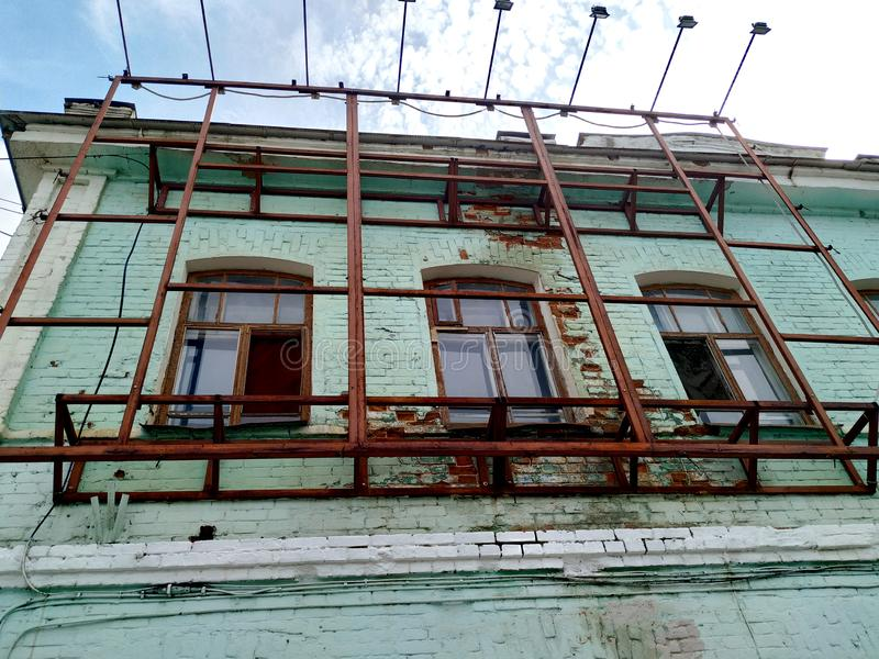 Upper floor the old brick building is painted with soft green paint. Window frames are wooden. Made of iron construction on top of royalty free stock photos