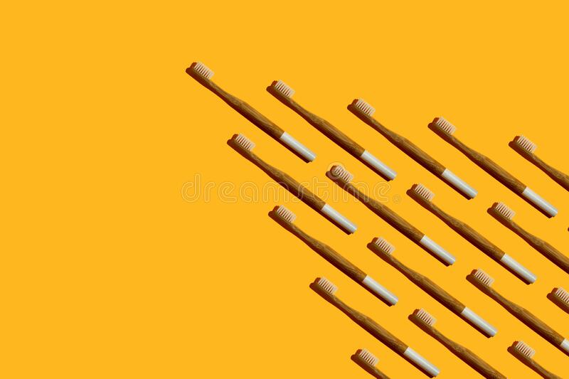 Wedge or arrow shaped bamboo toothbrushes on yellow background stock photos