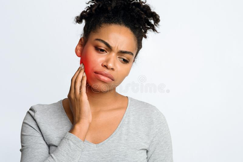 Woman suffering from inflamed gums, grey background. Dental problems. Afro woman suffering from inflamed gums, touching her cheek, grey background, free space royalty free stock photos
