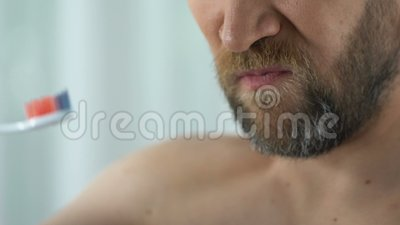 Bearded man feels tooth pain while cleaning teeth, showing toothbrush with blood. Stock footage stock video