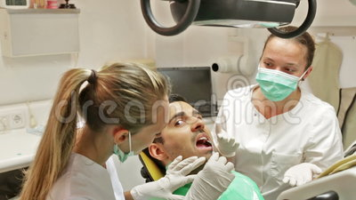 Dentist, assistant and scared patient. Portrait of doctor and frightened patient at dental clinic stock video footage