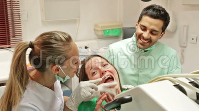 Dentist, assistant and scared patient at surgery. Office stock video