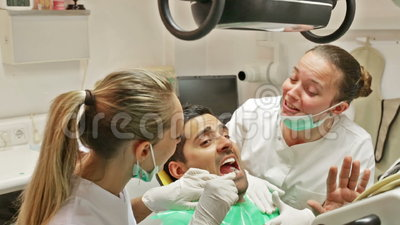 Dentist, assistant and scared patient. Terrified client and dental clinic crew during check up stock footage
