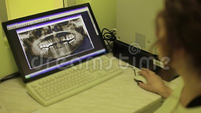The doctor looks at a snapshot of teeth. On the screen stock video footage