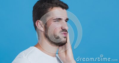 Portrait of young guy suffering from tooth pain. Dentistry and healthcare. Portrait of young guy suffering from tooth pain, holding his sore cheek, blue studio stock footage