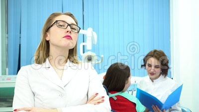 Woman in white medical coat standing in front of a camera at dentist office with a patient and another doctor talking on. Background. Chief physician of stock footage